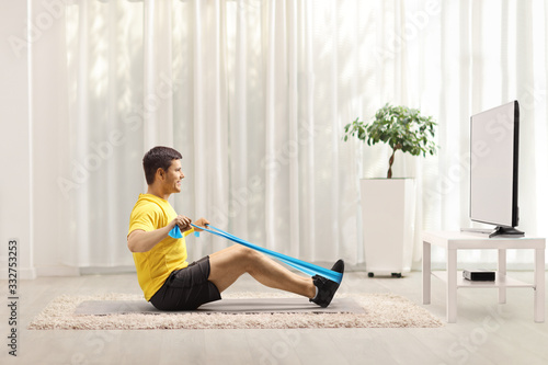 Fototapeta Man exercising with an elastic band in front of a TV at home obraz
