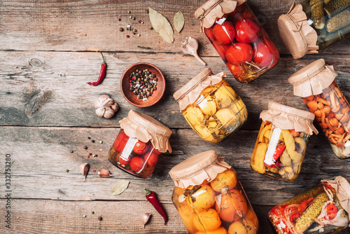 Canned and preserved vegetables in glass jars over wooden background Wallpaper Mural