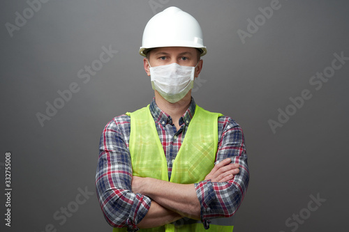 Fotografering Worker man wearing hygienic mask and protective hard hat.