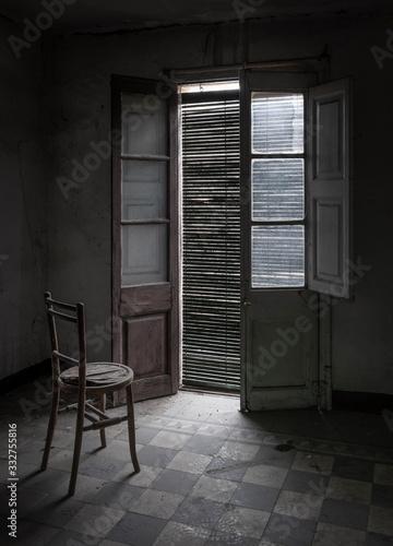 Habitación de casa abandonada con ventana, persiana y silla en la penumbra Canvas Print
