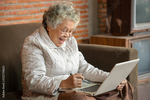 Fototapeta Happy Asian retired woman use notebook in living room at home. obraz