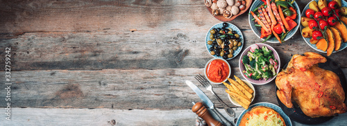 Fototapeta Roasted whole chicken or turkey, pumpkins, corn and harvest vegetables with kitchen knife and cutlery served around aged wooden cutting board on dark rustic background, frame. Thanksgiving Day food obraz