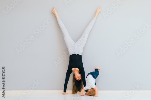 Sportive brunette mother with baby son doing press exercise on grey yoga mat over gray wall background Wallpaper Mural