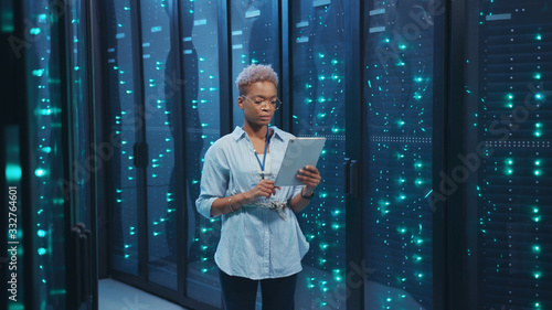 Fotografía Afro-american female IT administrator walking in server corridor diagnosing hardware system performance in data center cyber secure storage
