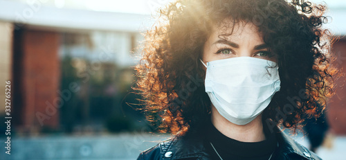 Obraz Close up portrait caucasian businesswoman with curly hair is looking at camera while wearing a protective mask - fototapety do salonu