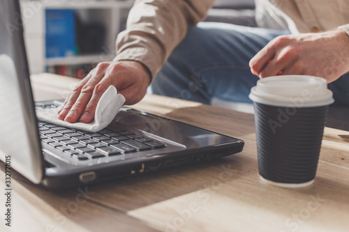 Obraz Man disinfects his laptop, cleaning keyboard . Wipe with rubbing alcohol spray and disinfectant - fototapety do salonu