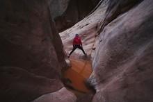 Adventurous Active Female Exploring Red Rock Sandstone Slot Canyon