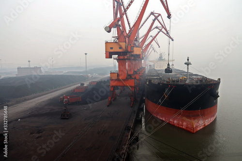Photo Cargo terminal for discharging coal cargos by shore cranes during foggy weather