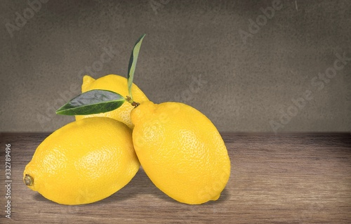 Fresh ripe juicy whole yellow lemons with green leaf on the desk