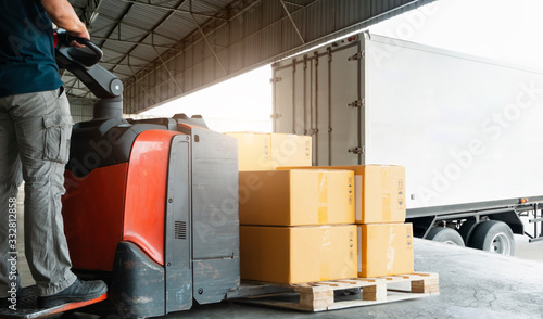 Fotografia Forklift driver loading pallet shipment goods into a truck, package boxes, Road