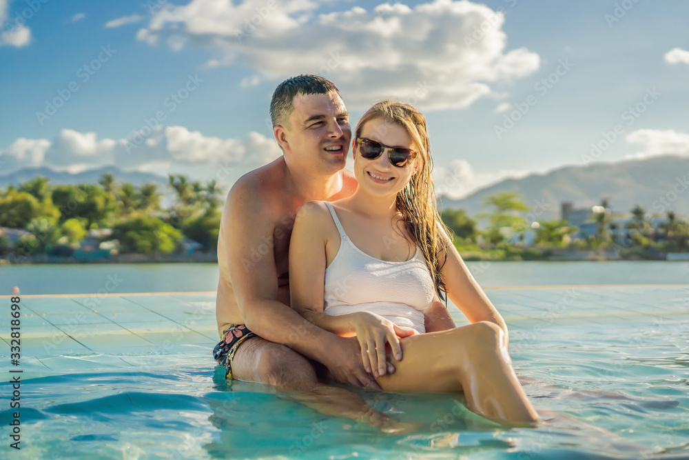 Fototapeta Luxury resort swimming pool. Happy couple tourists relaxing in holiday retreat on summer travel vacation enjoying ocean background
