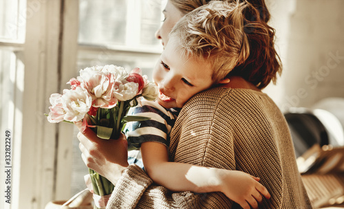 Fotografia Happy mother with flowers hugging little son.