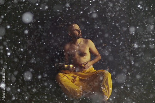 Tibetan singing bowl, a monk in yellow pants meditates and plays the musical bow Canvas-taulu