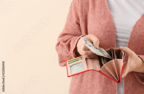 Fototapeta Senior woman with wallet on color background, closeup obraz