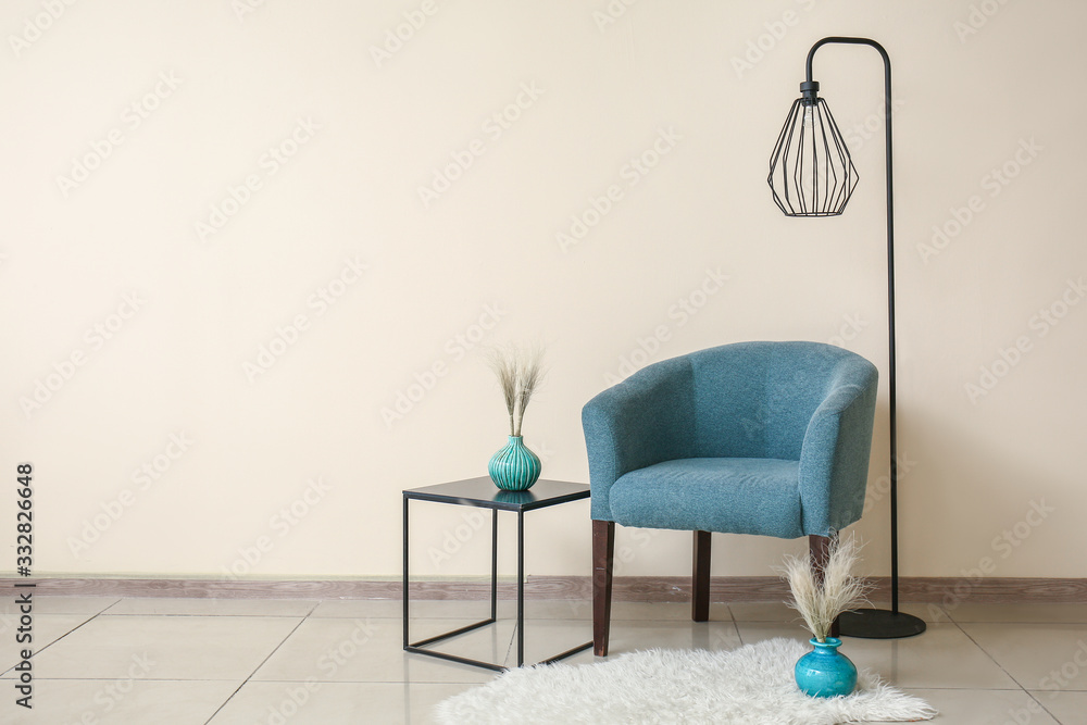 Fototapeta Comfortable armchair, table and lamp near color wall