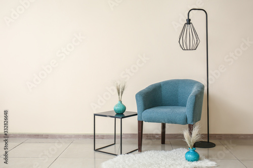 Obraz Comfortable armchair, table and lamp near color wall - fototapety do salonu