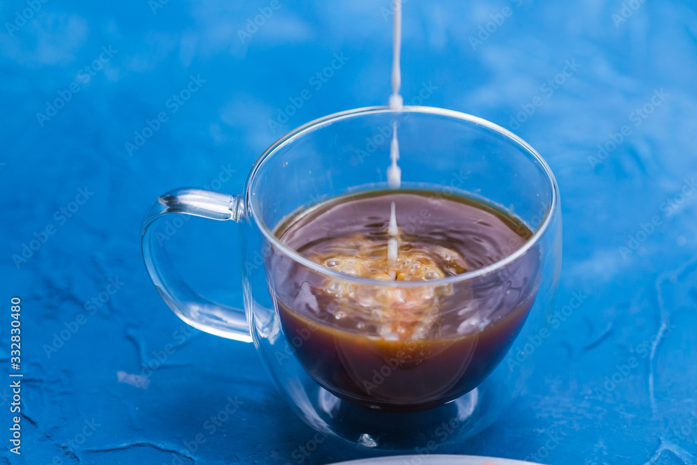 Fototapeta Morning and breakfast concept - Pouring cream into a cup of coffee