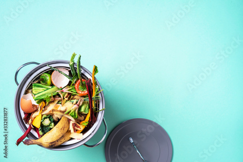 Fototapeta Top view of kitchen food waste collected in recycling compost pot. Peeled vegetables on chopping board, white compost bin on blue background. obraz