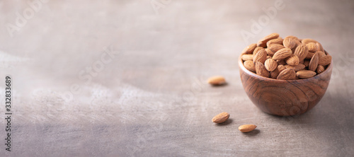 Fototapeta Almond nuts in wooden bowl on wood textured background. Copy space. Superfood, vegan, vegetarian food concept. Macro of almond nut texture, selective focus. Healthy snack obraz