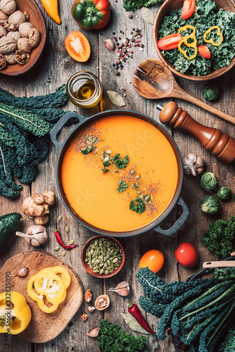 Fototapeta Vegan diet. Autumn harvest. Healthy, clean food and eating concept. Zero waste. Pumpkin soup with vegetarian cooking ingredients, wooden spoons, kitchen utensils on wooden background. Top view obraz