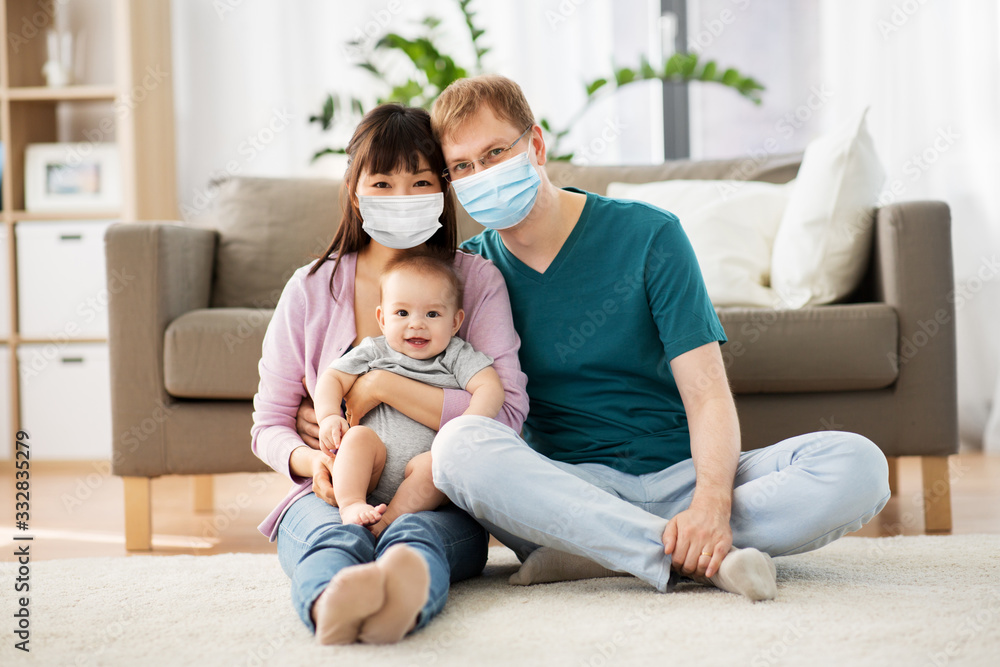 Fototapeta health, safety and pandemic concept - happy mother and father with baby wearing protective medical mask for protection from virus disease at home