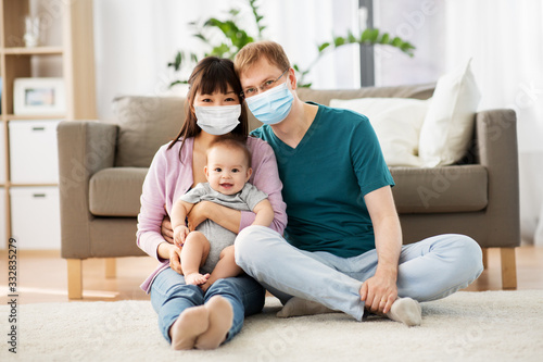 health, safety and pandemic concept - happy mother and father with baby wearing protective medical mask for protection from virus disease at home
