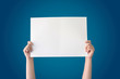 hand holding white blank paper isolated on blue gradient background with clipping path