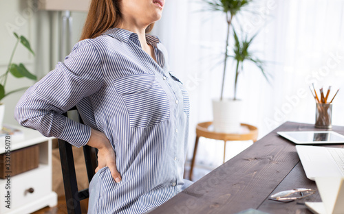 Fotografía Freelancer young woman suffering with back pain