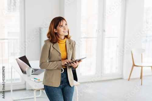 Fotografie, Obraz Young businesswoman holding a tablet pc