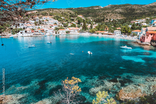 View on tourquise transparent bay of mediterranean village Assos framed through green pine grove. Shadow pattern. Kefalonia Greece