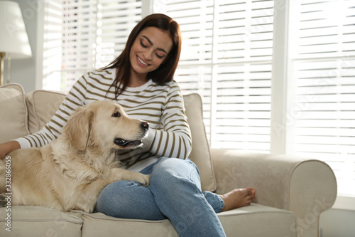 Fototapeta Young woman and her Golden Retriever on sofa at home. Adorable pet obraz
