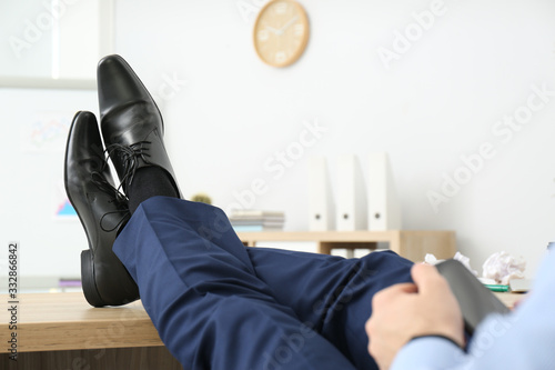 Lazy office employee with mobile phone at workplace, closeup Canvas Print