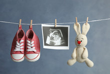 Pair Of Child's Booties, Ultrasound Photo And Toy Bunny Hanging On Laundry Line Against Dark Background