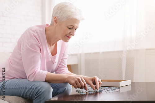Senior lady playing jigsaw puzzle at home, empty space Fototapet