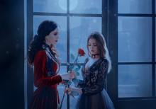 Brunette Vampire Woman Gives Red Rose Cute Medieval Beauty Blonde Girl Princess. Backdrop Fairy Night Window Moon Light. Elegant Vintage Gothic Dress. Art Holiday Mystic Makeup. Horror Halloween Image