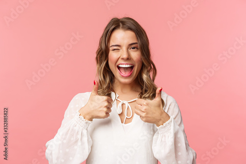 Portrait of sassy good-looking blond girl assure all good, show thumbs-up and wi Canvas Print