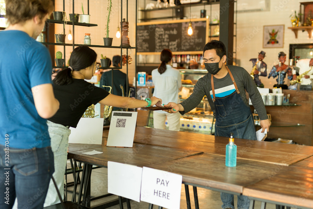 Fototapeta Social distance conceptual small business waiter serving customer in cafe.