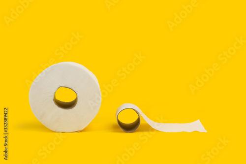 Foto Rollo de papel higiénico vacío y usado junto a un rollo completo de papel higiénico sobre fondo amarillo brillante aislado