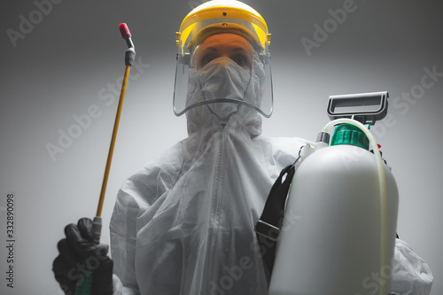 Fototapeta Scientist holding chemical sprayer for sterilization and decontamination of viruses, germs, pests, infectious diseases. obraz