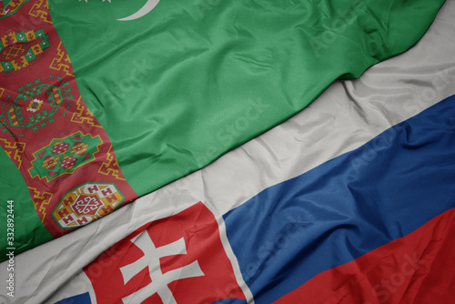 Photo waving colorful flag of slovakia and national flag of turkmenistan