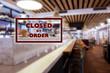 Closed due to coronavirus sign on defocused empty restaurant room