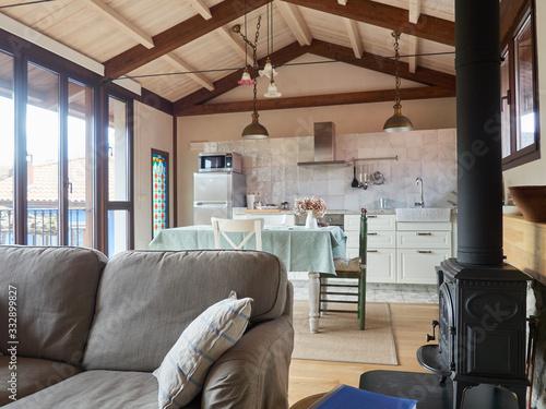 sofá gris en primer plano con cocina comedor al fondo techos altos de madera en Canvas Print