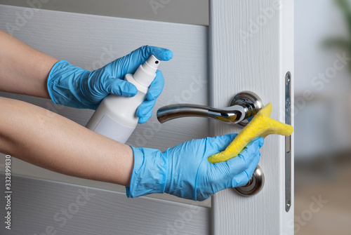 Obraz Cleaning door handles with an antiseptic during a viral epidemic - fototapety do salonu