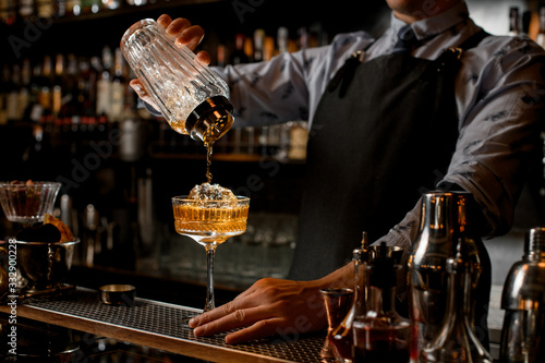 Canvastavla Professional bartender in black apron pours drink from shaker into glass
