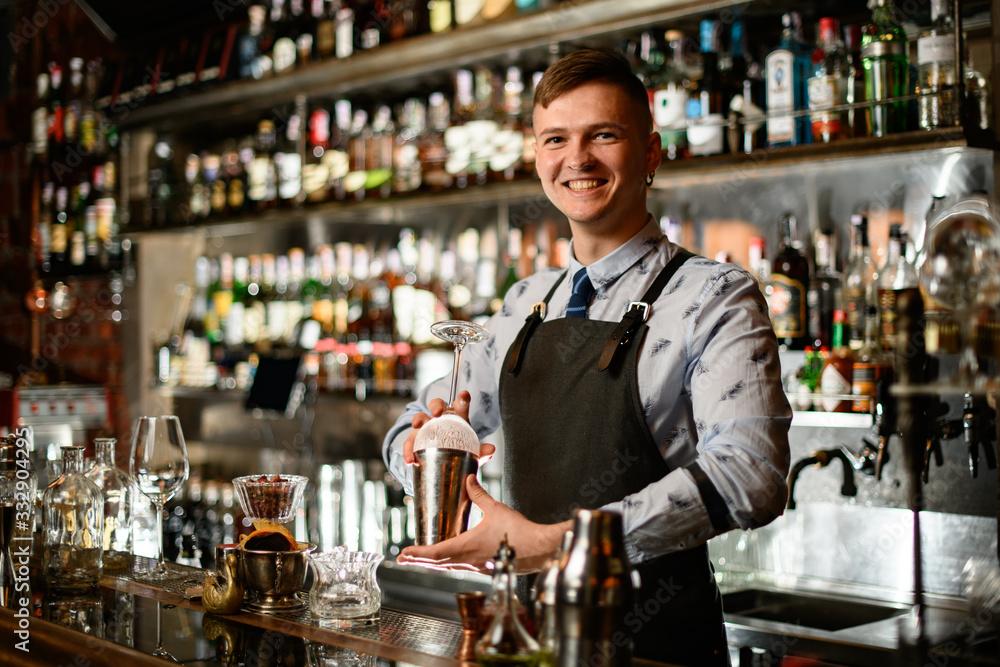 Fototapeta young smiling bartender in black apron preparing to make cocktail.