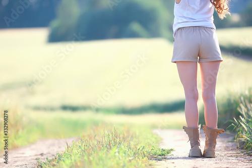 Fototapeta female legs in summer trekking boots / walks anonymously on the field woman big shoes girl obraz