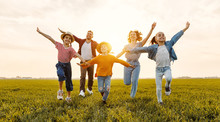 Happy Family Running In Field ...