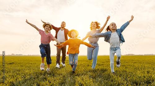 Fototapeta Happy family running in field in summer evening. obraz