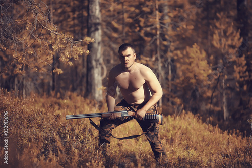 hunting man / hunter with a gun hunting in the autumn forest, yellow trees lands Wallpaper Mural