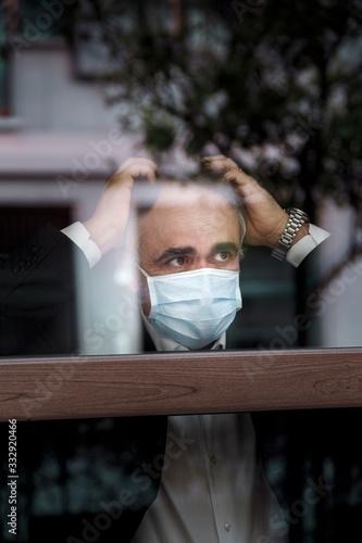 Uomo guarda attraverso un vetro con aria preoccupata e si mette le mani in testa Wallpaper Mural